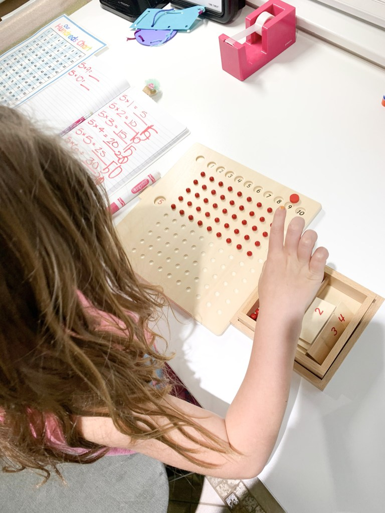 Elementary girl homeschool using manipulatives to do multiplication on bead board Montessori