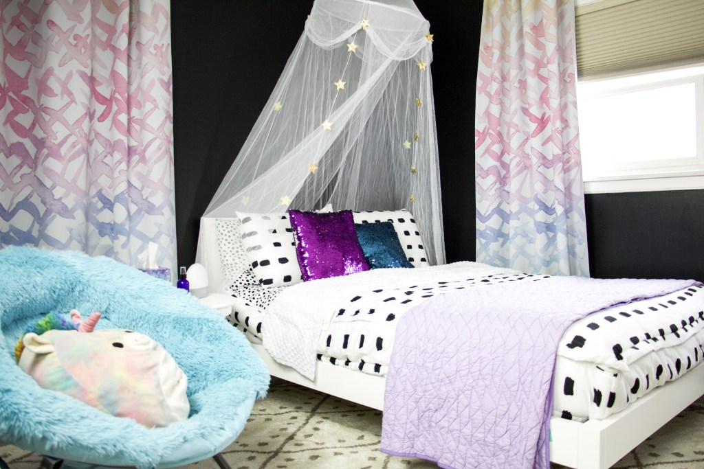 bed with white and black bedding, canopy, sparkly pillows, rug, watercolor curtains and fuzzy chair