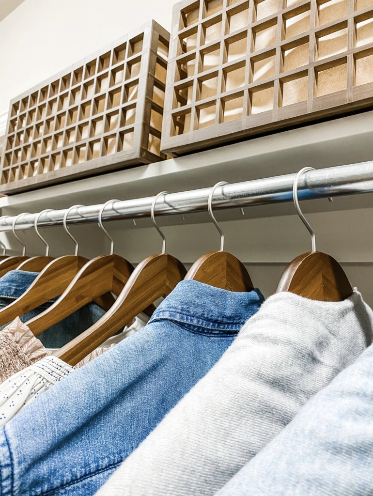 closet with wood hangers and bins