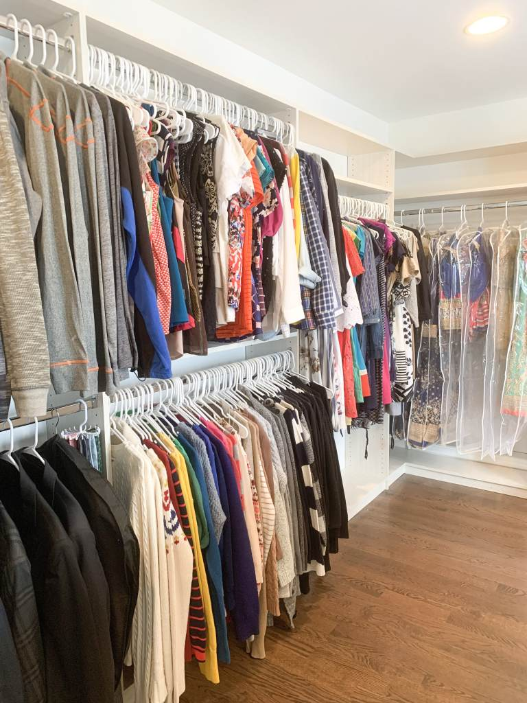color coordinated closet in an L shape with tops on the top hanging rack and pants on the bottom and dresses on the other side of the L in covered bags