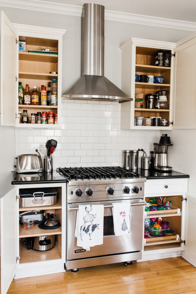 kitchen stove with cabinets and doors open with everything organized on shelves and in cabinets