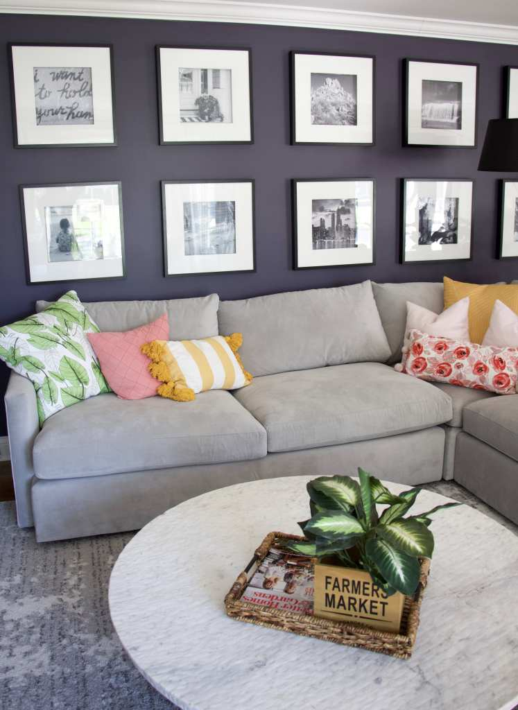 close up of sectional with green, pink and yellow pillows against a purple wall