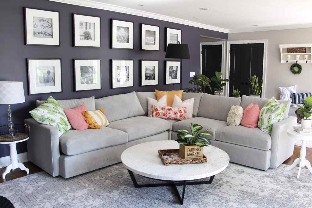 view of living room with dark purple walls, gallery wall, grey sectional with pink, green, and yellow pillows