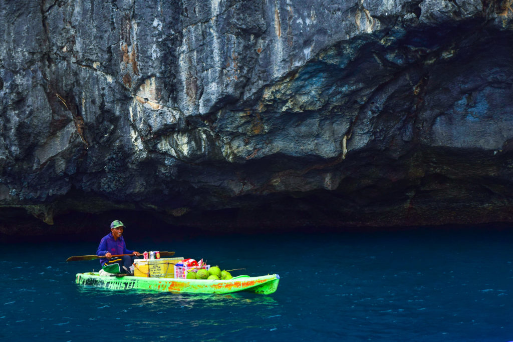 el nido floating store. local man selling buko juice and beer in the boat