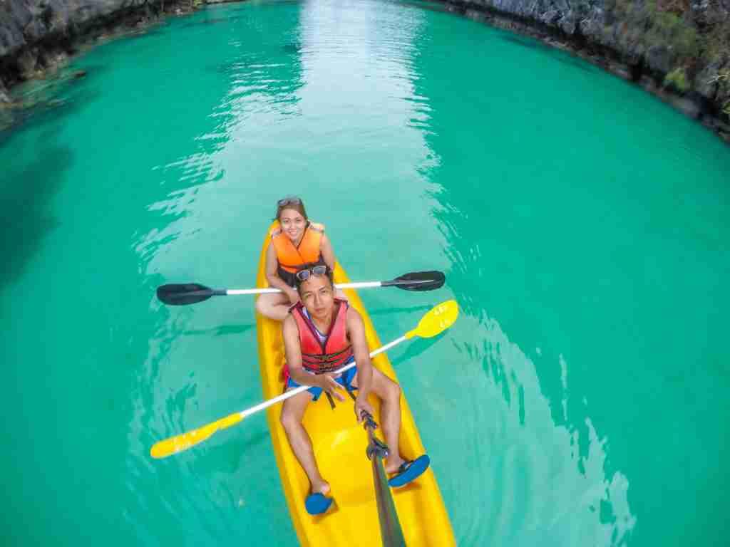 riding kayak in turquoise blue green water of big lagoon in el nido palawan