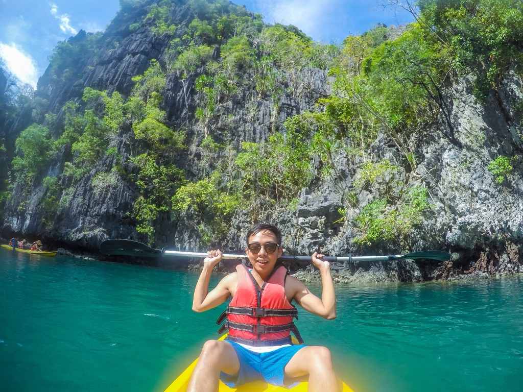riding kayak in turquoise blue green water of small lagoon in el nido palawan