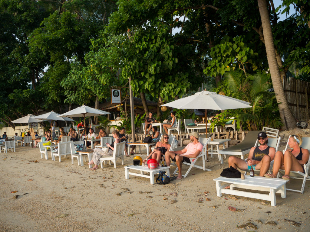 tourists chilling near the shore in marimegmeg beach el nido