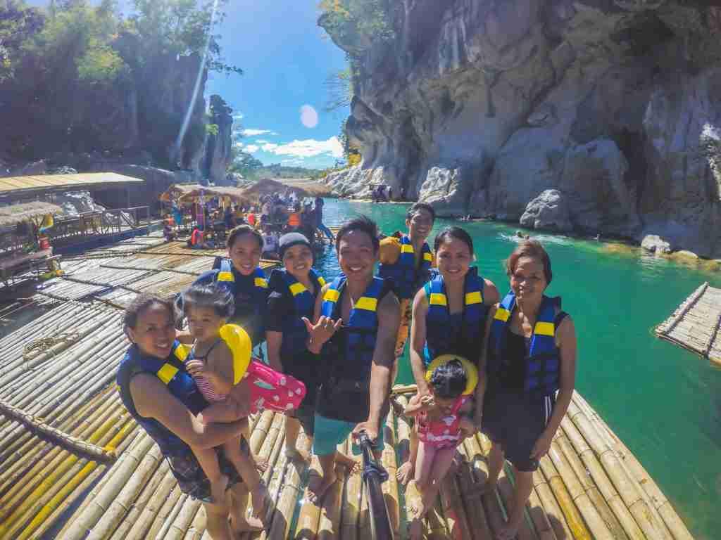 family swimming picture in bamboo raft in minalungao national park nueva ecija