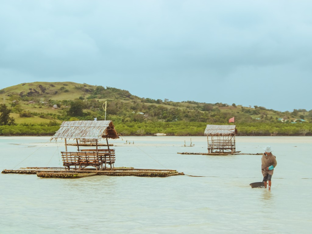 coastal dwellers selling seashells in manlawi sandbar with nipa huts
