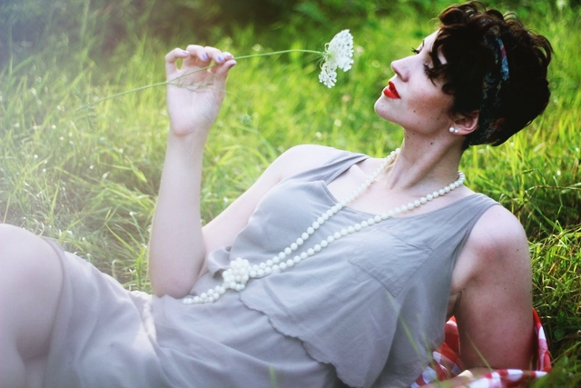 Vintage inspired outfit: Beige dress, long faux pearl necklace, vintage head scarf, red lipstick, sunny summer field