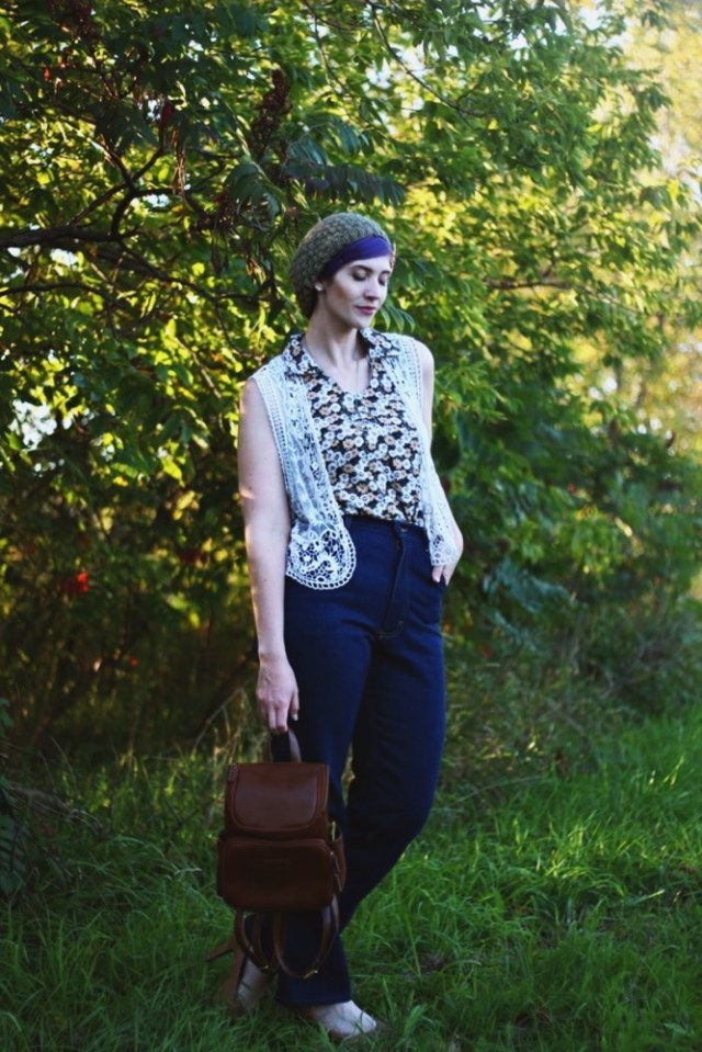 1970s Inspired Outfit: Floral blouse, white lace vest, high waisted dark wash denim, high heels, mini brown backpack