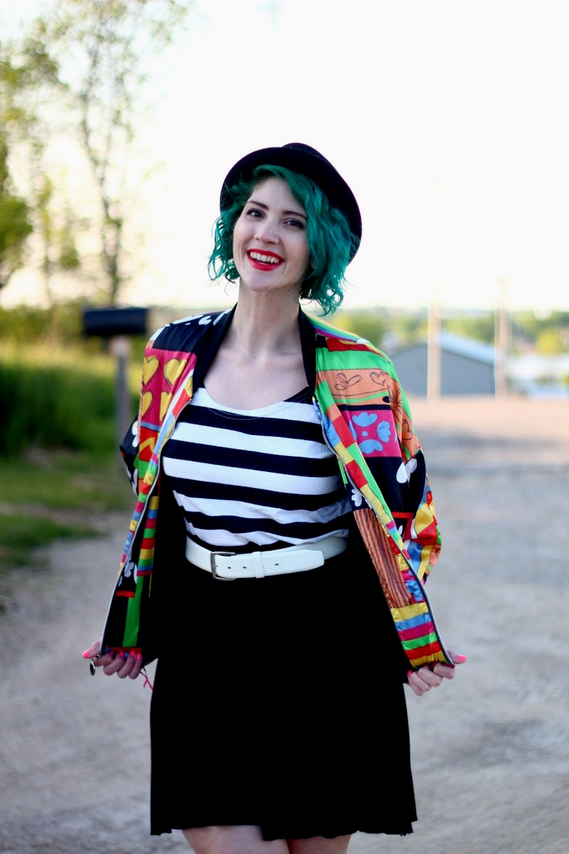 Outfit: brightly patterned jacket, striped top, black skirt, thick white belt, green hair, pork pie hat, red lipstick