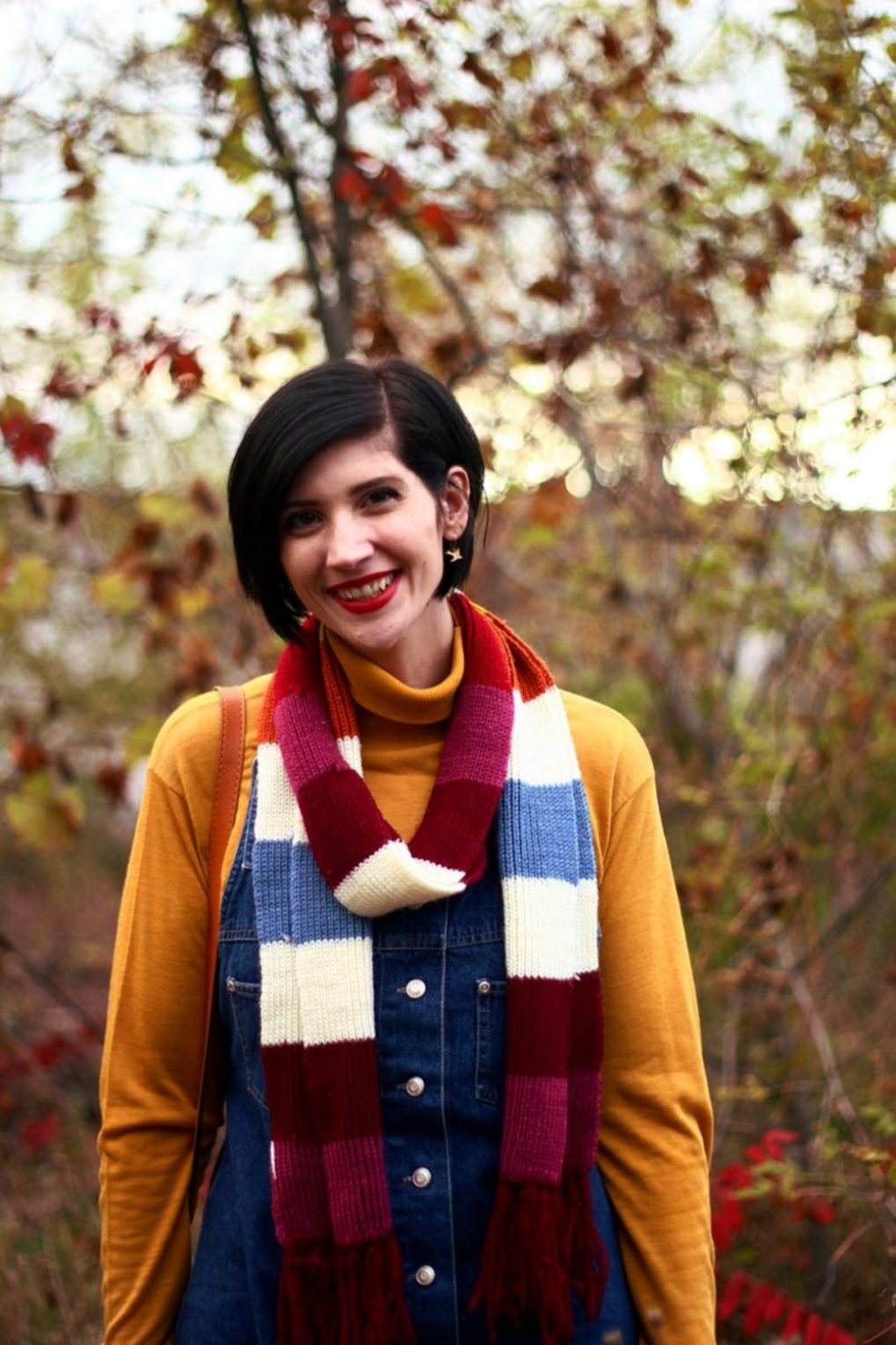Outfit: Mustard yellow turtleneck, denim overall dress, multi-colored striped scarf, red lipstick