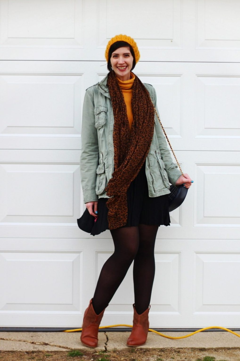 Outfit: mustard yellow turtleneck, olive green utility jacket, leopard print scarf, yellow knit hat, black skater skirt, black tights, cognac colored boots, navy blue quilted purse