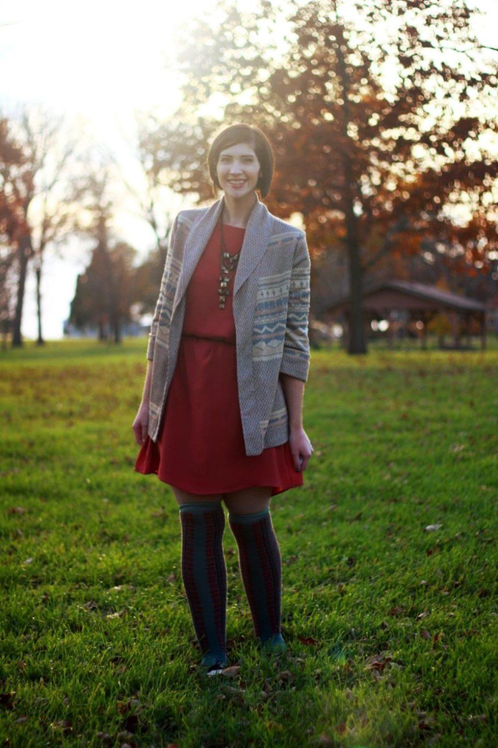 Outfit: Orange dress, beige belt, bronze necklace, patterned cardigan, otk colorful socks, brown flats