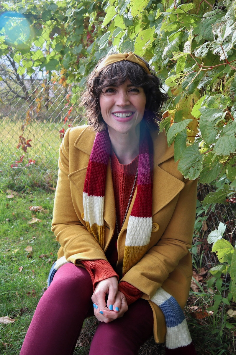 Hannah has short shaggy curls adorned with a yellow headband, in front of a leafy background, wearing an orange sweater, yellow jacket, and striped scarf