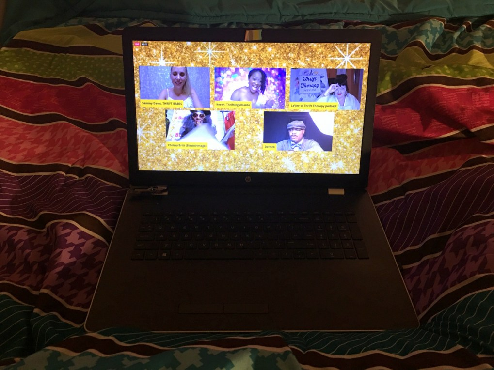 a laptop on a colorful bed comforter displaying a still from a live video during the Heart of Thrift Conference 2020