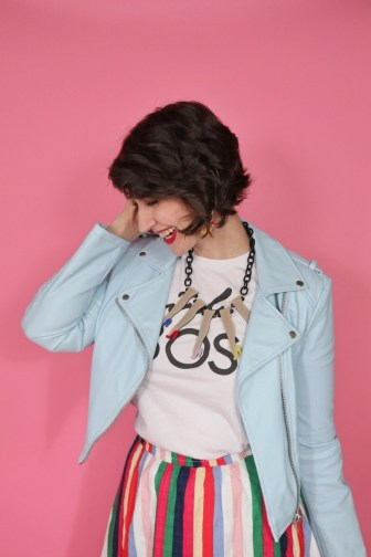 """Hannah Rupp looking down wearing a white thrifted """"girl boss"""" tee, statement necklace, and light blue leather moto jacket"""