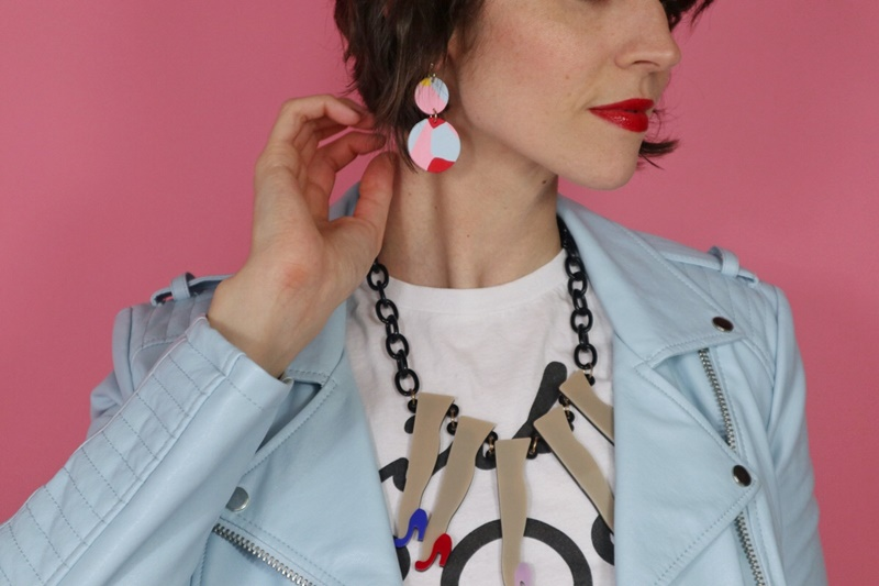 Hannah is wearing bright red lipstick, colorful polymer clay earrings, a statement necklace, and a light blue moto jacket