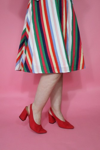 Hannah is wearing a thrifted knee length skirt on the bottom and red high heels
