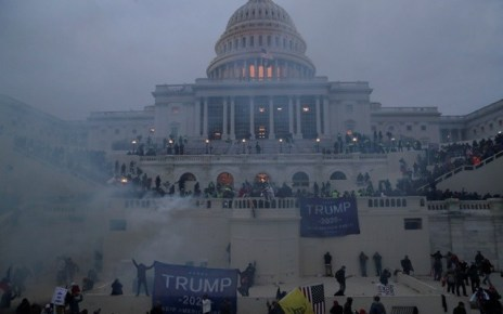 Image of the US Capitol building with tear gas and trump supporters in front of it.