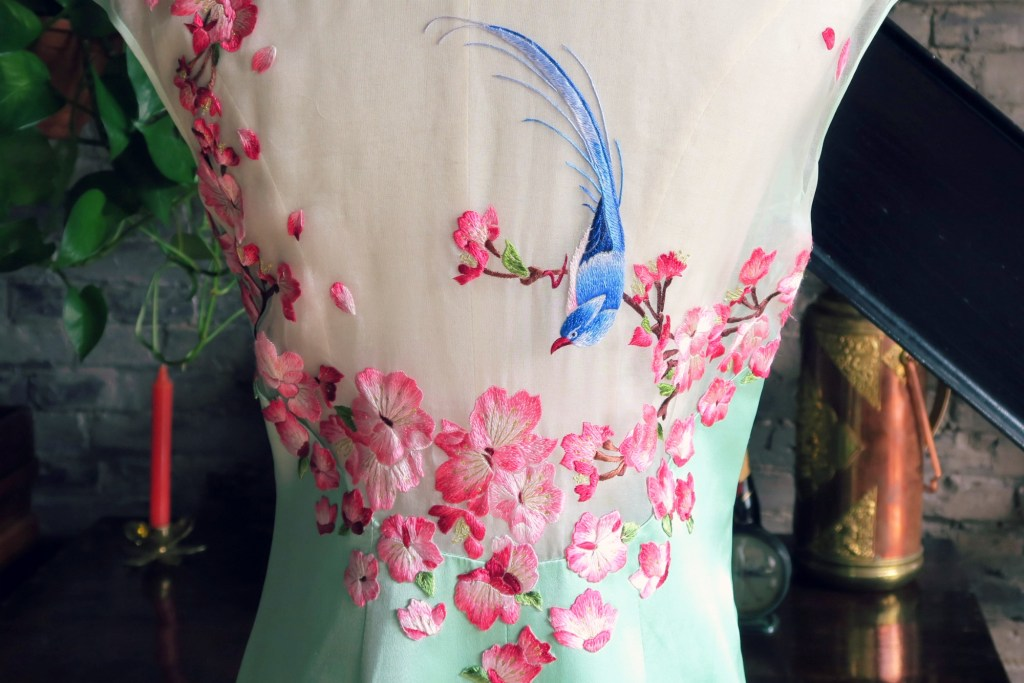 And a close up of the beautiful back. The flowers have amazing gradations of magenta and the bright blue bird livens the whole thing up.