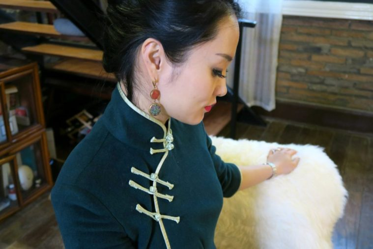Wearing forest green cashmere qipao with apple green edging and pankou