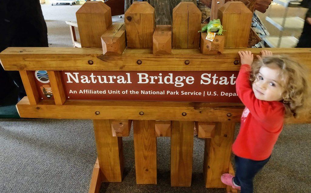 Sophie hanging on Natural Bridge State Park sign.