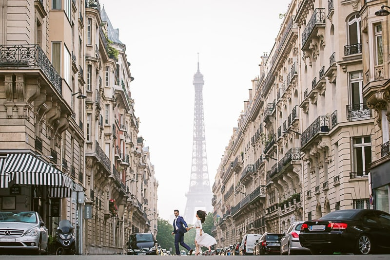 Newly engaged couple running across the street between two buildings and the Eiffel Tower in the background