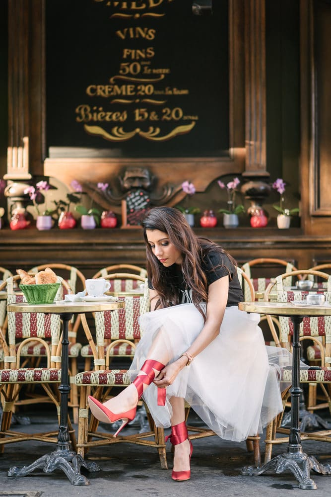 Paris portrait of a girl putting her red heels on in a Parisian cafe