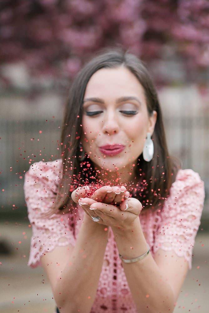 Pretty girl blowing in pink confetti in Paris