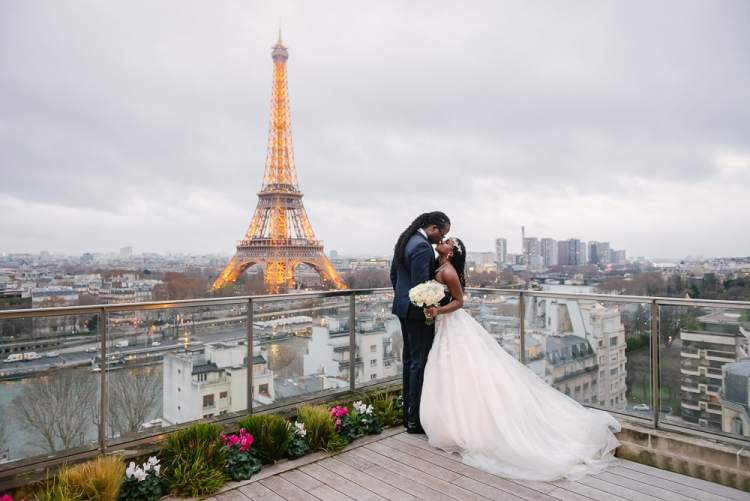 Paris elopement photographer - black bride and groom kissing on the terrace of Shangri La with Eiffel Tower in background