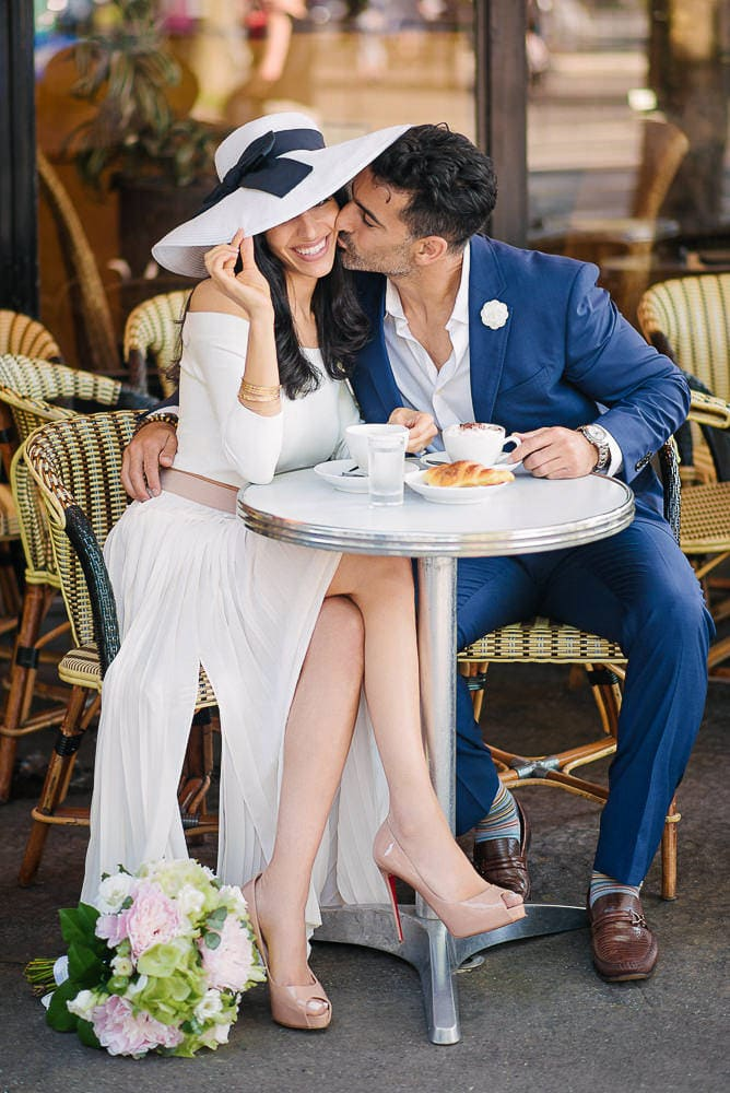 paris photographer engagement - beautiful girl with white hat being kissed on the cheek by her fiance