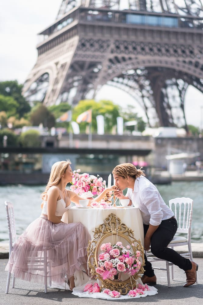 photo shooting couple with beautiful table scape containing roses and candles by the seine river in front of the eiffel tower