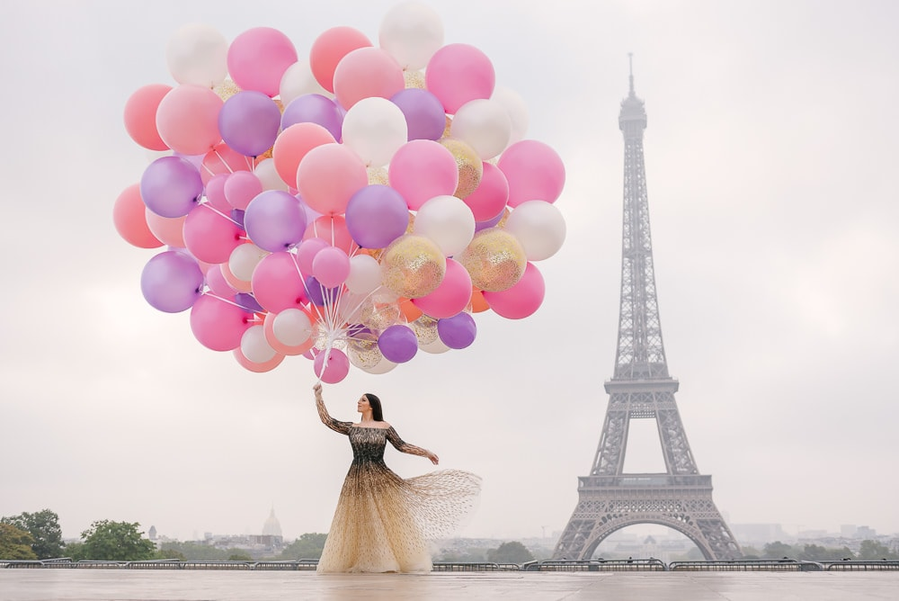 Bride with a huge bouquet of colorful balloons dancing in Paris