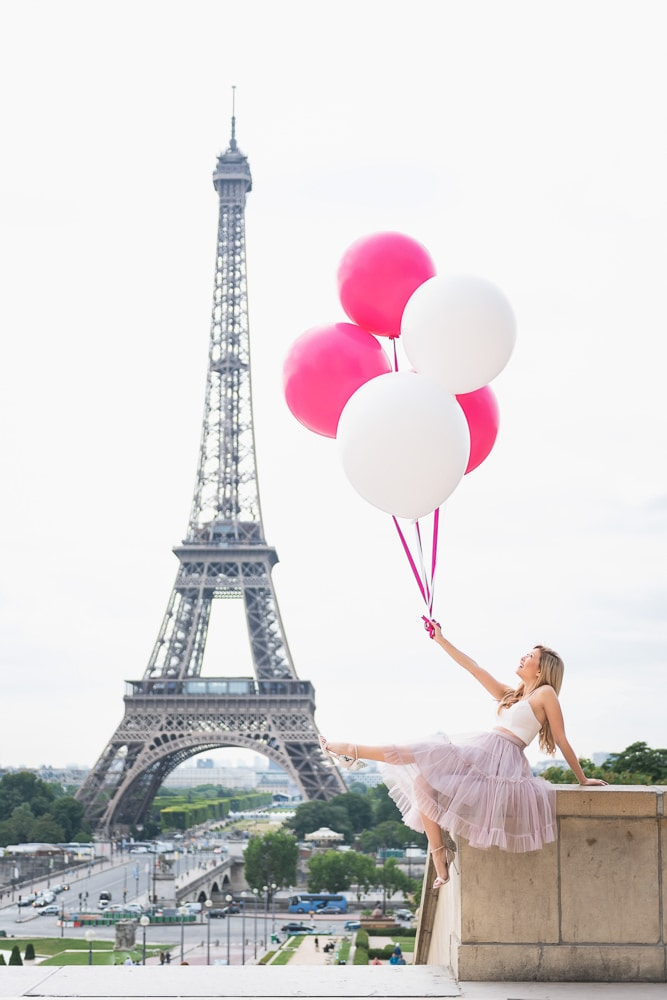 Pretty girl wearing pink tutu dress holding pink balloons at the Eiffel Tower