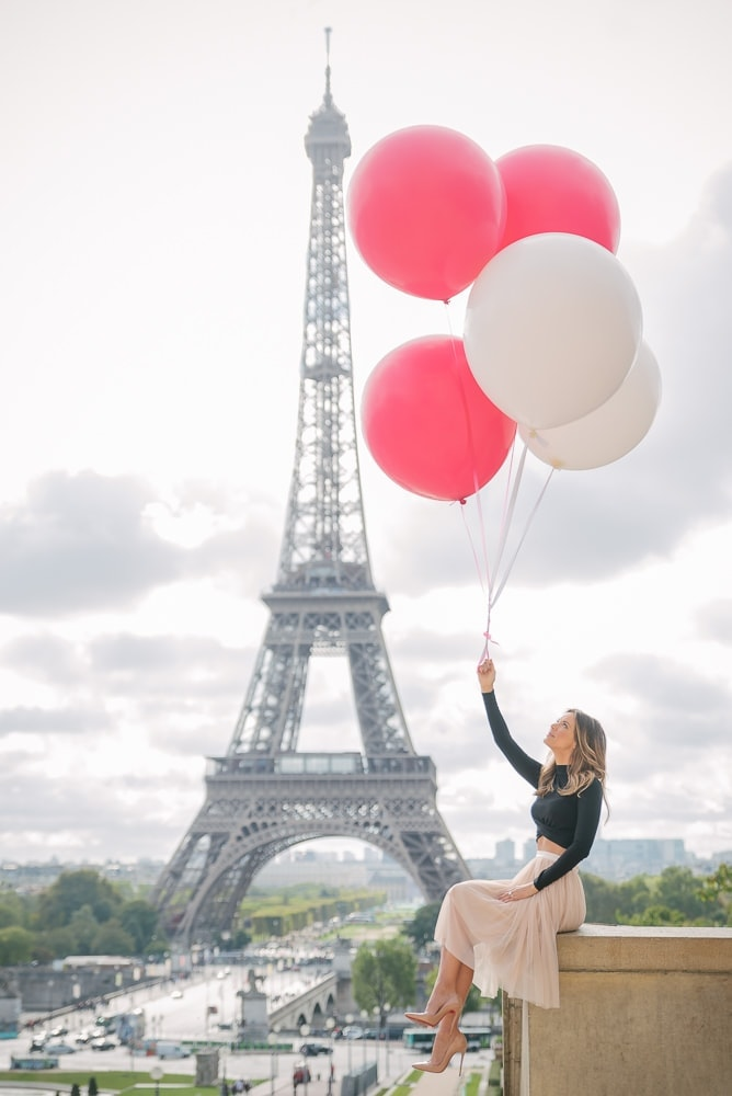 Beautiful girl holding red and white balloons in front of the Eiffel Tower