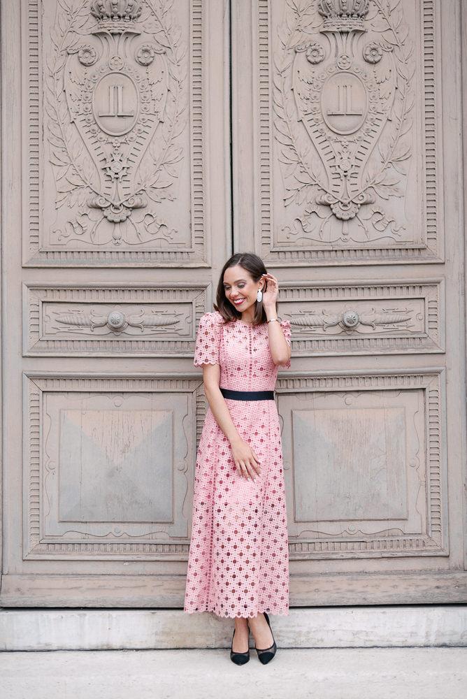Beautiful girl in pink dress posing in front of old door in Paris