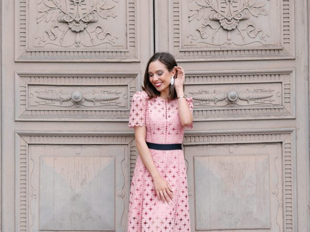 Beautiful girl in pink dress posing in front of old door in Paris