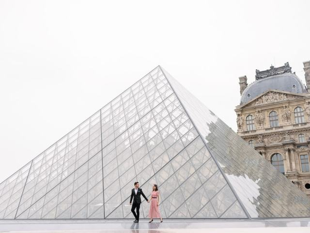 Couple walking on water in front of the big pyramid of the Louvre Museum