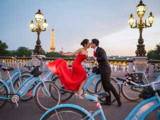 Pictures couples – Asian couple kissing on blue bikes on the Alexander 3 bridge in Paris