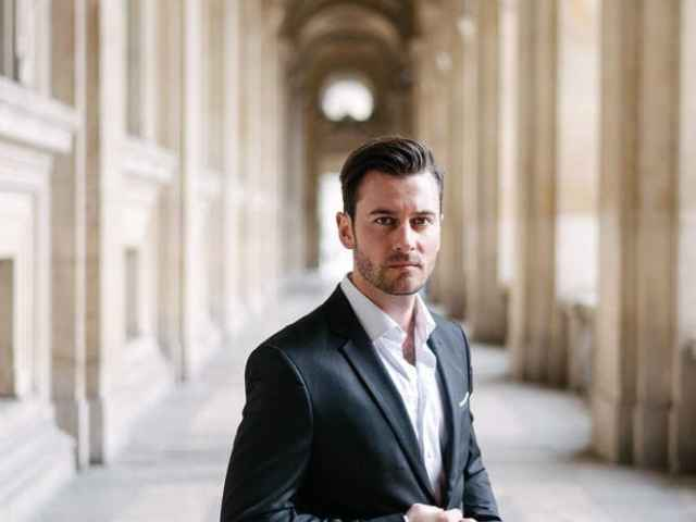 couples portrait ideas - young man posing under the arches of the Louvre Museum