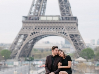 fun couple photoshoot ideas - sitting on a wall in front of the Eiffel Tower