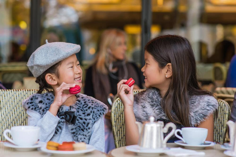 two asian kids eating macarons in paris