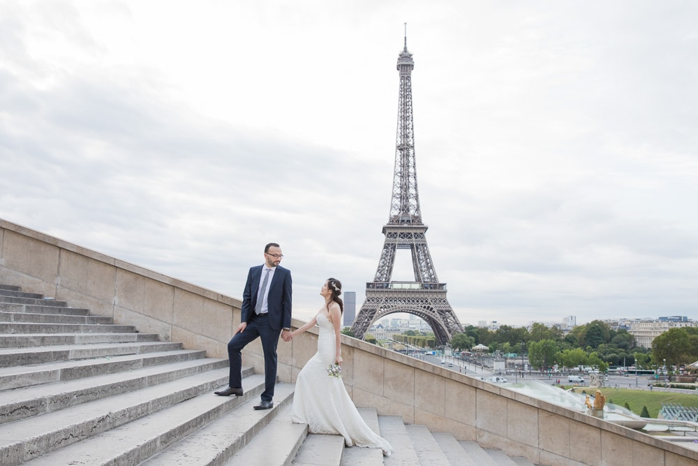 Bride and groom walking the steps in front of the Eiffel Tower in Paris, France