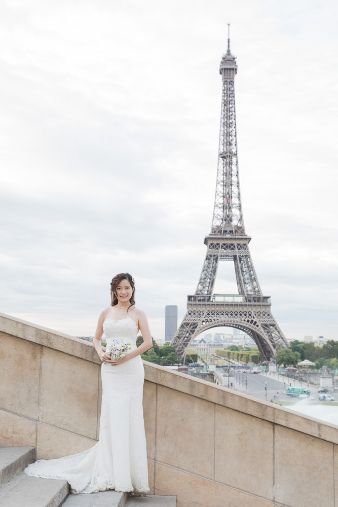 Asian bride holding bouquet in front of the Eiffel Tower
