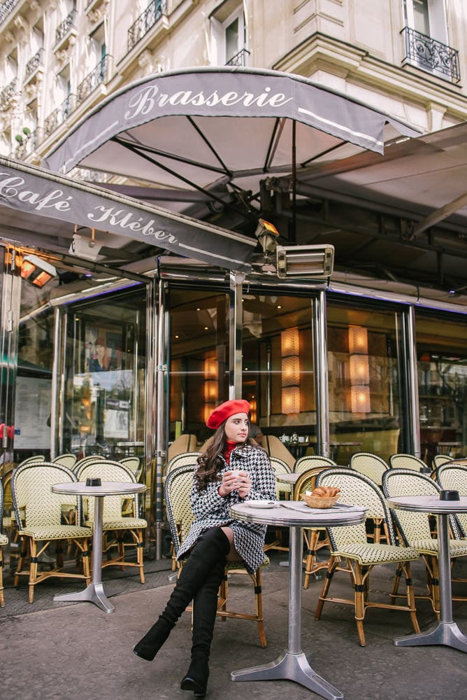 Girl wearing red french beret posing in a parisian cafe for her quince photos