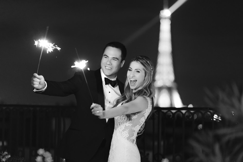 Happy newly married couple celebrate their Paris elopement with sparkles on a private terrace at the Peninsula Paris hotel