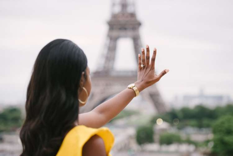 Newly engaged girl looking at diamond ring on her hand at the Eiffel Tower in Paris