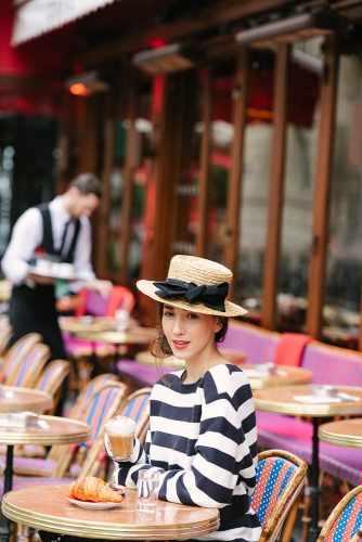 Influencer Fabmuse Diana posing for portraits in a parisian café